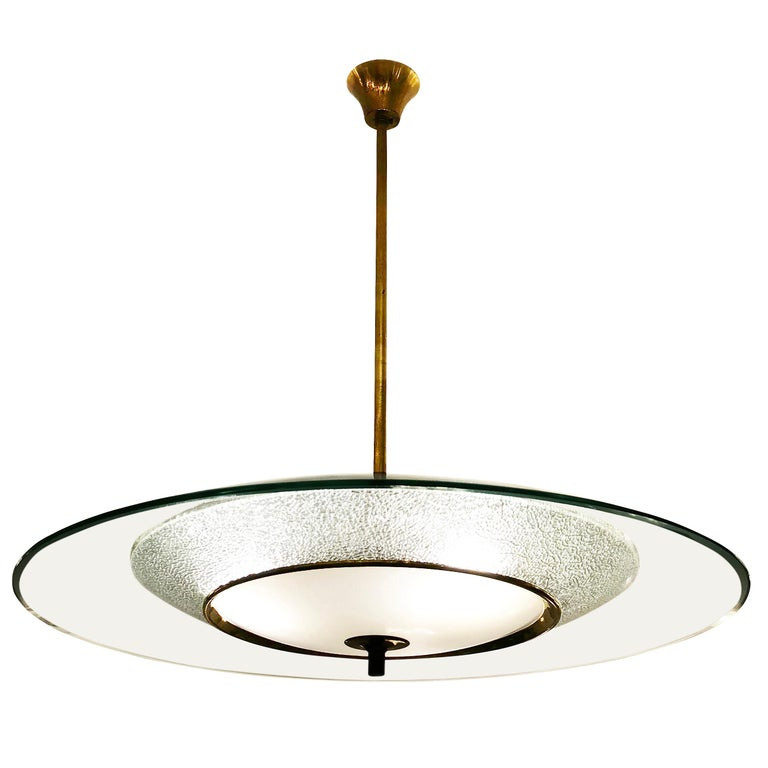 Italian midcentury ceiling light reminiscent of the work of Fontana Arte. The top concave glass is clear with beveled edges, the second has stunning texture and the third is white with a brass rim to hide the three light sources. Hardware is