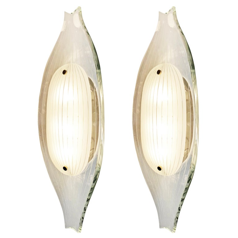 Fontana Arte wall lights model 2340 deigned by Max Ingrand in the 1960s. Each one is composed of a thick hand polished glass with on top a white oval glass. Both glasses have thin etched lines the follow the sloping shape of the fixture. Hardware is