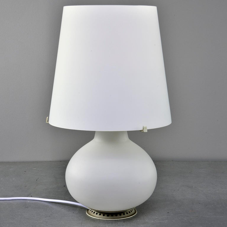 Designed by Max Ingrand for Fontana Art in 1954, this all white satin glass lamp lights up inside both the base and at the standard socket. New wiring for US electrical standards. No cracks, chips or flaws found. 
