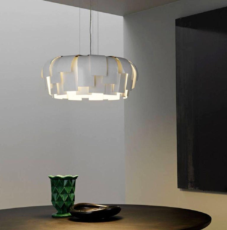 Wig suspension features a diffuser made up by a composition of curved petals in white glossy varnished metal. Lower diffuser disc in satin methacrylate. Adjustable hanging cables in steel. Three 60-watt, 120 volt A19 medium base halogen bulbs are