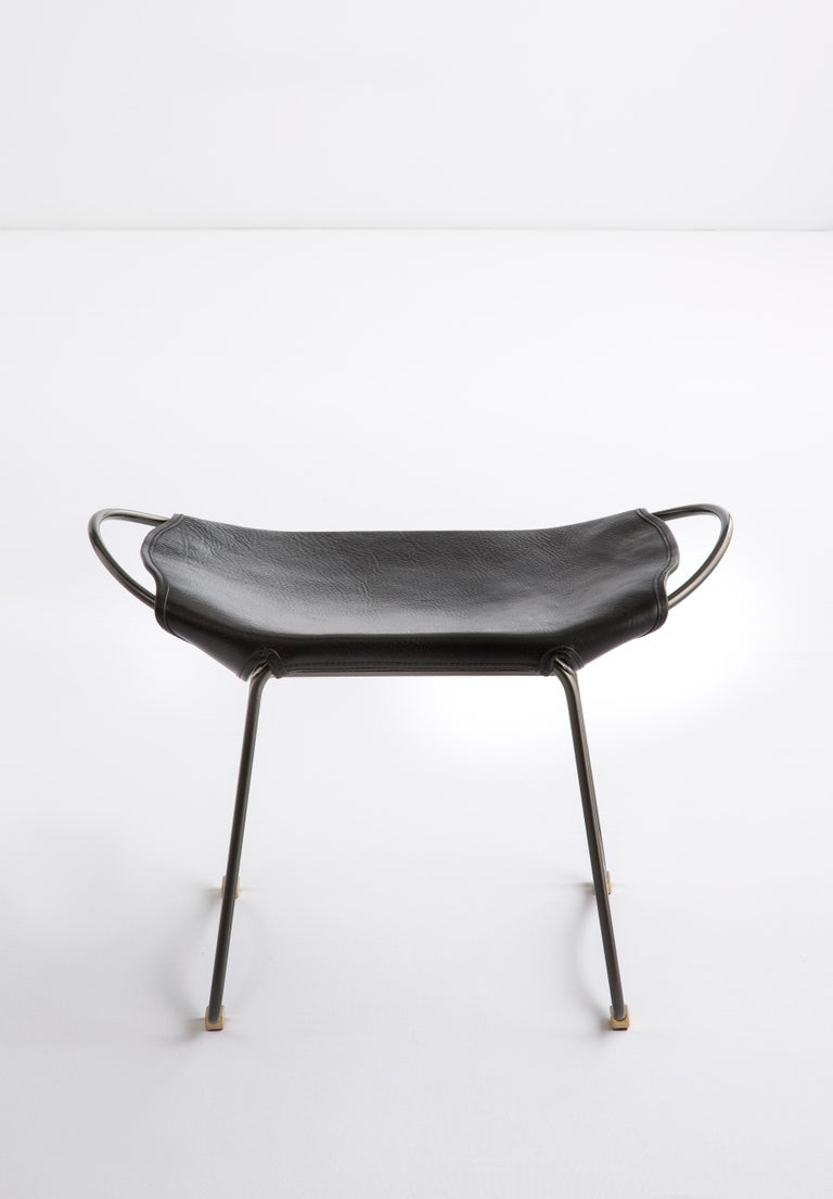 HUG Footstool Black Smoke Steel and Vegetable Tanned Black Saddle Leather  The HUG footstool is designed and conceived with a light aesthetic, the slight oscillation of the steel rod of 14 mm is complemented by the flexibility of the 3.5 mm thick