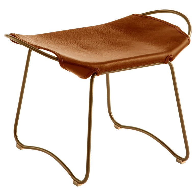 Hug footstool old silver steel and vegetable tanned natural tobacco leather  The Hug footstool is designed and conceived with a light aesthetic, the slight oscillation of the steel rod of 14 mm is complemented by the flexibility of the 3.5 mm