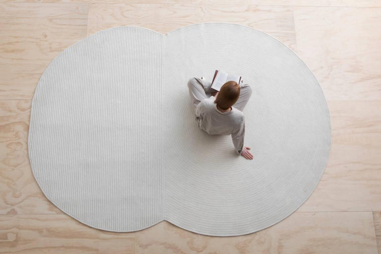 A braided wool rug composed of a simple circle and oval shape bound together. Each shape explores a subtle contrast in braiding technique with the circle made of a flat braid coil and the oval made of cable lock braided rows with a contrasting zig
