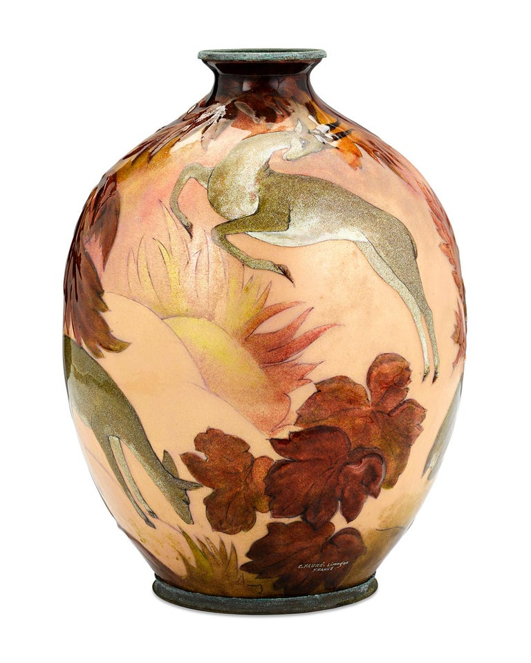 A group of graceful deer are the subject of this charming enamel on copper vase by famed French decorative artist, Camille Fauré. The deer sit against a backdrop of a forest in autumn, highlighting Fauré's deep appreciation for nature which is