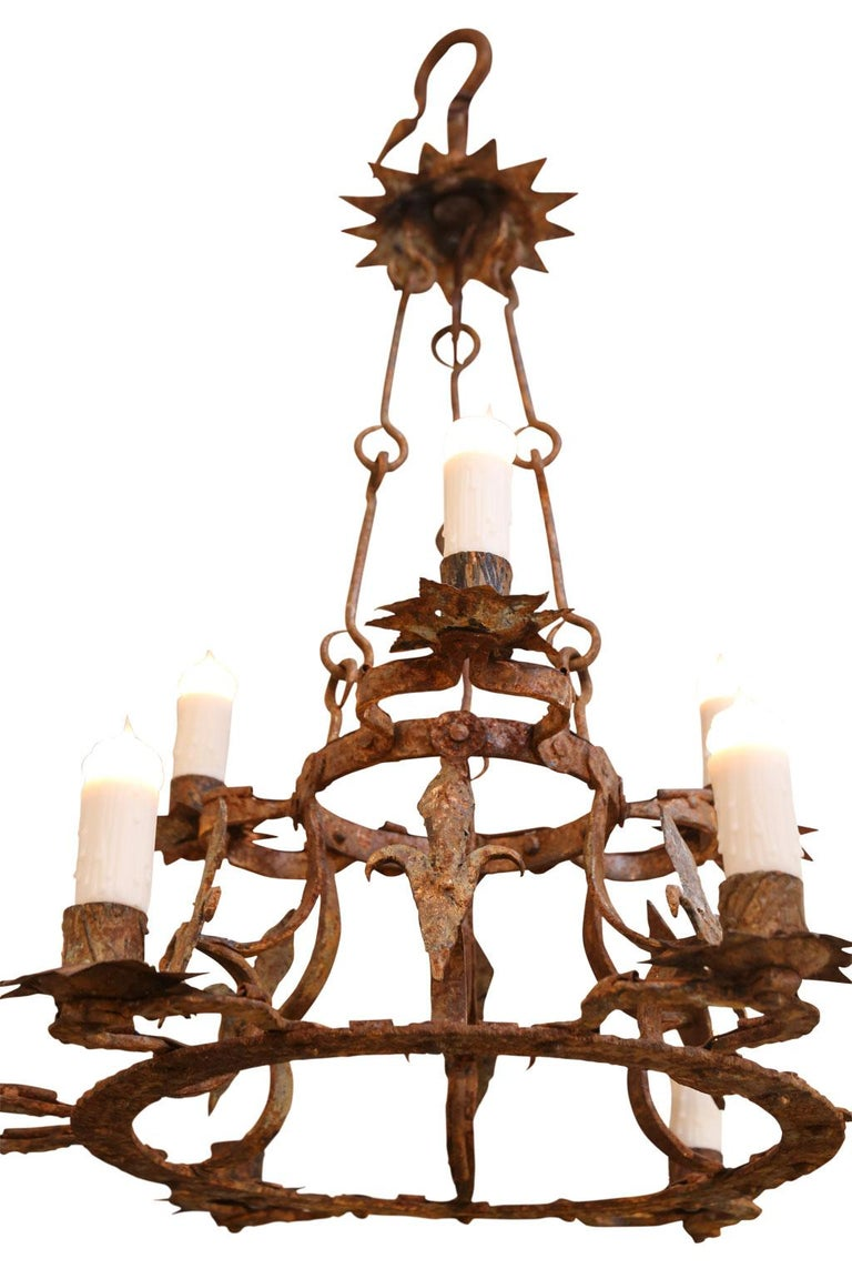 Forged iron two-tier chandelier with nine lights (three upper tier and six lower tier), tole bobeches, fleur d'lis motif and remnants of old gilt. Newly-wired and includes extra chain and a canopy.