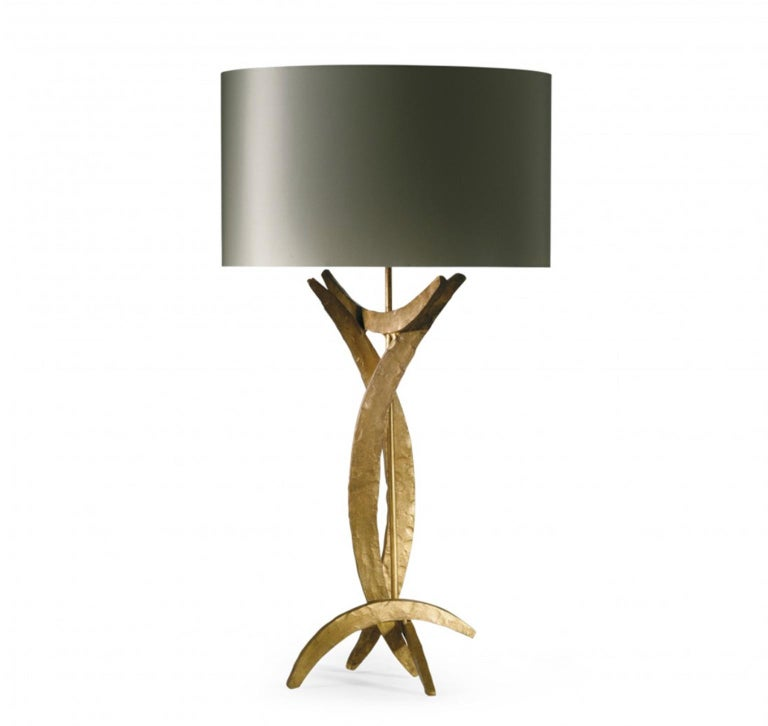 This steel forged table lamp has a raw shape with its metal parts in bright gold finish or burnished one. In the photo is visible the bright one. The contrast is stronger with the presence of the silk oval lamp shade. This Brutalist style table