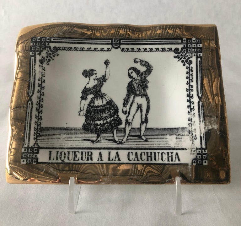 Offered is a white and gold porcelain pin tray by Piero Fornasetti with an Italian advertising label theme of man and woman in black. This collectible item would look great on a bedside table, dressing room table, bar cart and practically any area