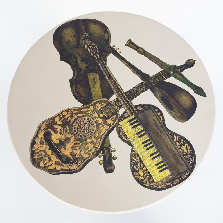 """Pair of round side tables, tops with musical instruments motif and bases in brushed brass, by Piero Fornasetti, Italy, 1950's (labels on bottom read """"Fornasetti-Milano""""). Bases have been cleaned and polished."""