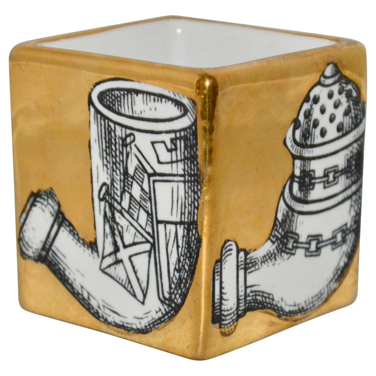 Fornasetti pipe holder in gold and with pipe motives around the sides.