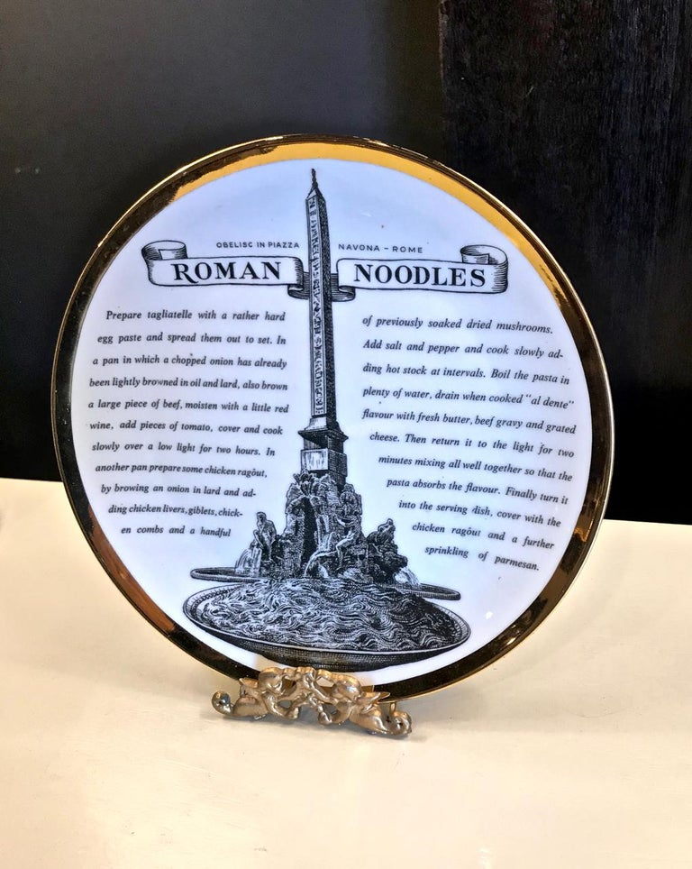 This is a superb set of eight Fornasetti Recipe plates (English Version). The plates depict various Italian cities and monuments and each carries a recipe for a culinary regional favorite. The plates are rimmed with a gold band.