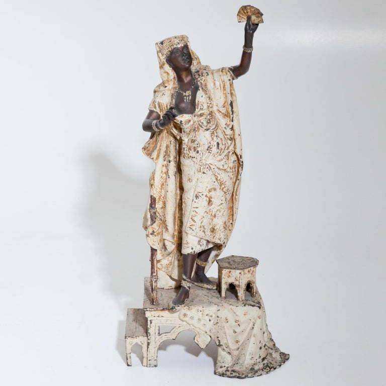 Group of two Moors, carrying large cauldrons and a female fortune teller in white robes standing on a small pedestal. Zinc cast iron, partly white painted. (Fortune teller 68 x 33 x 22, moors 44 x 23 x 18 / Ø23.)