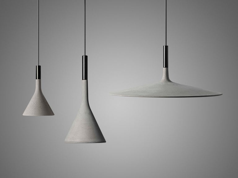 Suspension lamp with direct light. Cement diffuser, consisting off a special amalgam colored with pigments, produced by pouring the fluid mixture into a mold rose with galvanized metal bracket and batch dyed ABS cover. Black electrical cable and