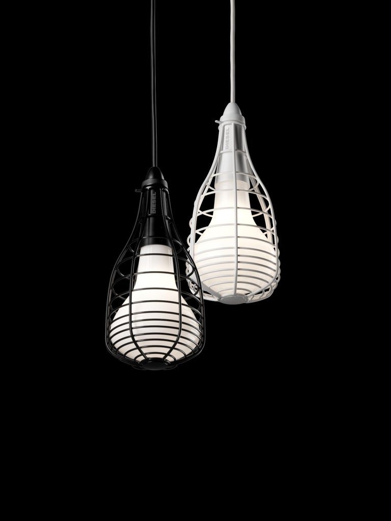 """The micro Cage lamp has an """"underground"""" origin in the real sense of the word. It is inspired by the lamps of miners and workers, protected by a metal cage which in Cage becomes a decorative element, thanks to its artisan craftsmanship, which can be"""