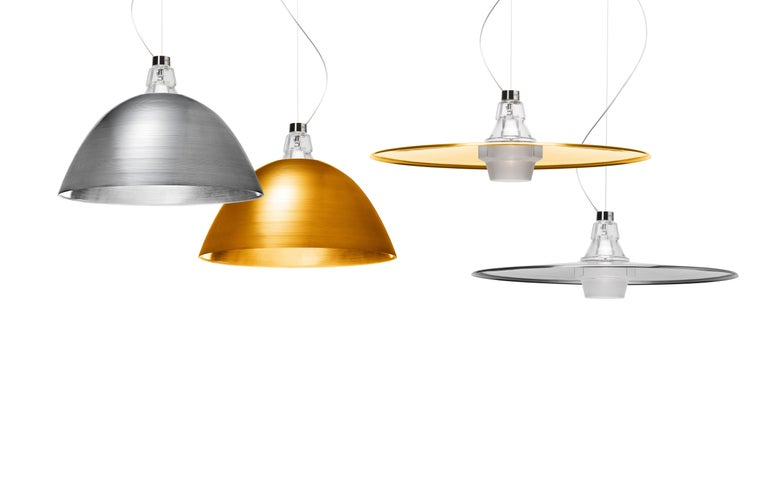 Suspension lamps with semi-diffused and direct down light. Diffuser made of transparent hand-blown glass, the lower half of which is also sandblasted by hand. The two reflectors are made of a slab of aluminum, turned in a steel mold to ply it into
