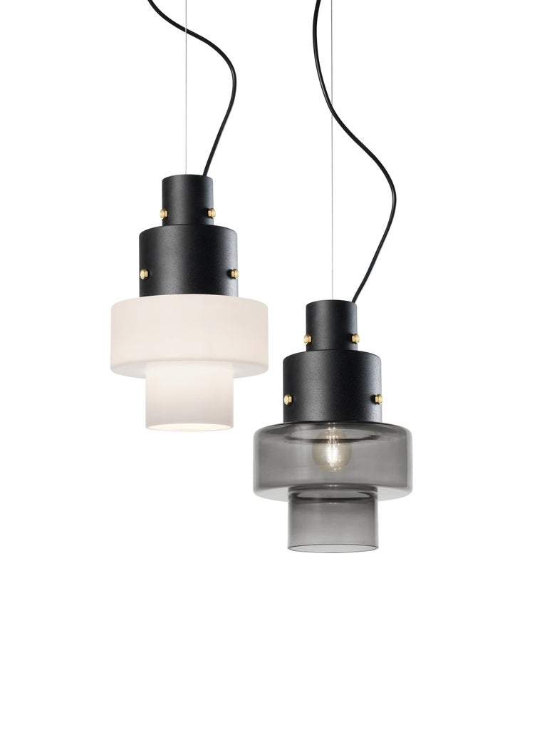 Gask is a small suspension lamp with a grand personality. The steel mount, with its rough and textured embossed black finish, is joined to the blown glass diffuser with exposed brass bolts, which recall the atmosphere of an old-fashioned hardware