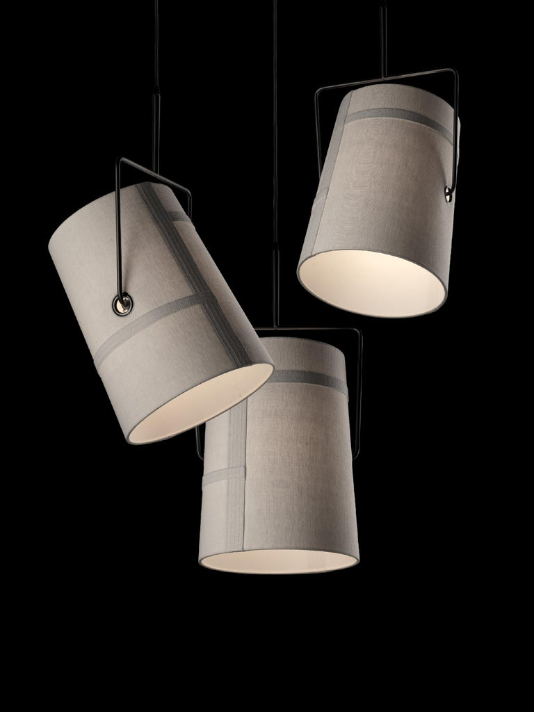 Suspension lamp with diffused and direct light. The outline of the matte satin finish polycarbonate diffuser is covered with pure linen fabric, with a purposely-uneven weft and warp of the fabric achieved by hand. The fabric is stained and undergoes