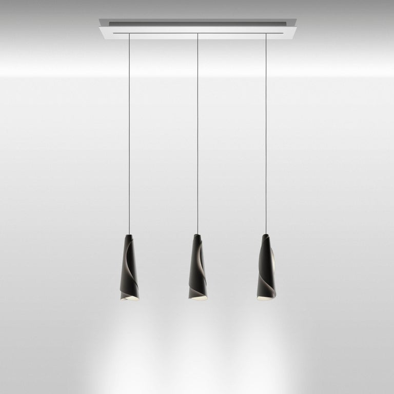 Suspension lamp with direct light. Diffuser consisting of two laser-cut aluminum sheets, which are rolled up and slipped into one another. The engravings on the diffusers let the light out, to delineate the contours of the two sheets with a glow of