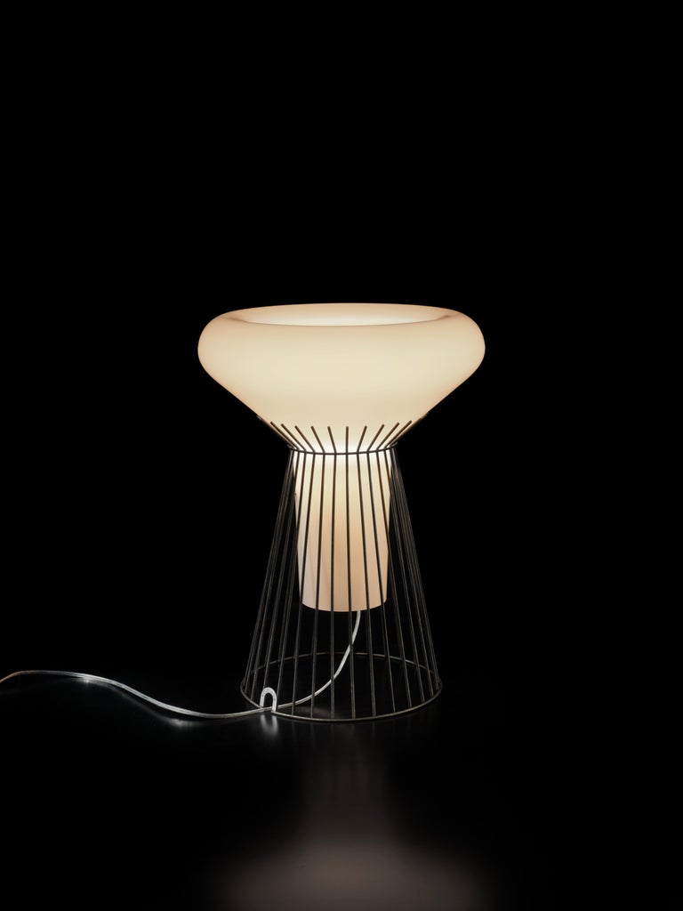 Mysterious and charismatic, the table lamp Metafisica consists of a diffuser in blown glass in soft, full form seemingly suspended from a delicate metal cage. When switched on, the diffuser appears to float in the air defying gravity. Its warm,