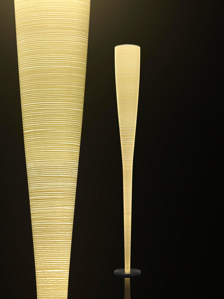 Floor lamp with diffused and indirect light. Diffuser achieved using an artisanal process that entails the application of a Kevlar® thread for the yellow version and a carbon thread for the black version onto a glass fabric. Internal metal rod; the
