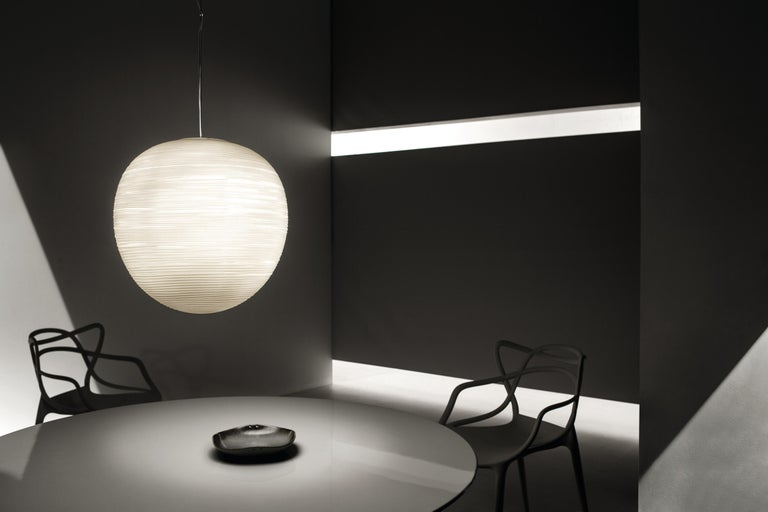 Incised with surface engravings that recall a large oriental lantern, the Rituals extra large blown glass suspension lamp stands out for its generous dimensions and its soft, warm glow.  Materials: Blown engraved satin glass and varnished