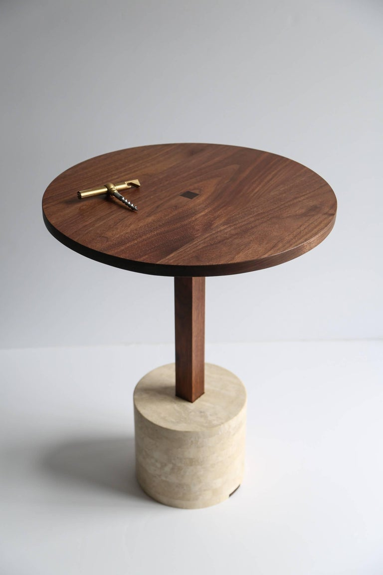 This modern yet classic design pairs the age old materials of stone and wood by placing them in honest relation to each other. The hefty stone bases create a weighted foundation for the light weight wooden stems and table tops.  Available with a
