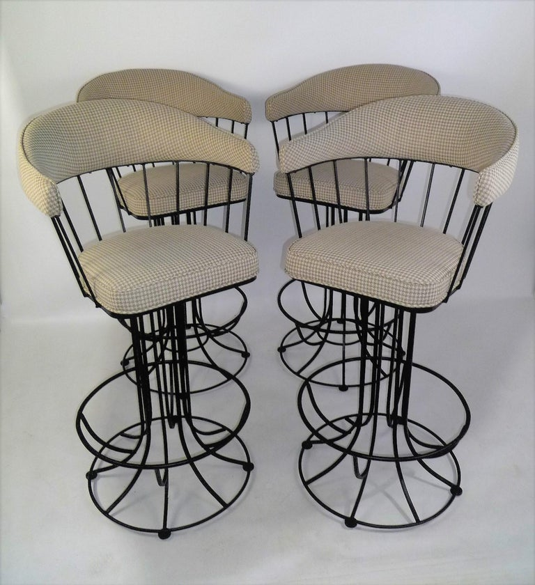 Wonderful 1960s swiveling barstools reminiscent of the shape and style created by Anton Lorenz. In shaped blackened iron, they have a circular design from the spindle back down to the bases. Freshly upholstered curved back and arms and seat in a