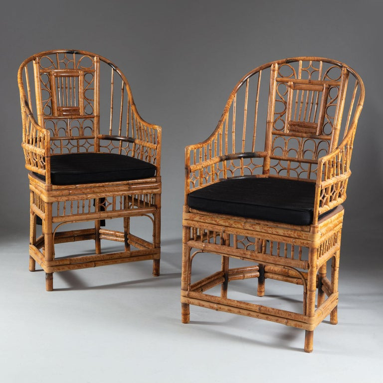 A set of four mid-20th century bamboo armchairs, the horseshoe backs with intricate scrollwork decoration, raised upon legs with conjoining stretchers. Together with squab cushion seats.  These chairs show stylistic influence of the suites of