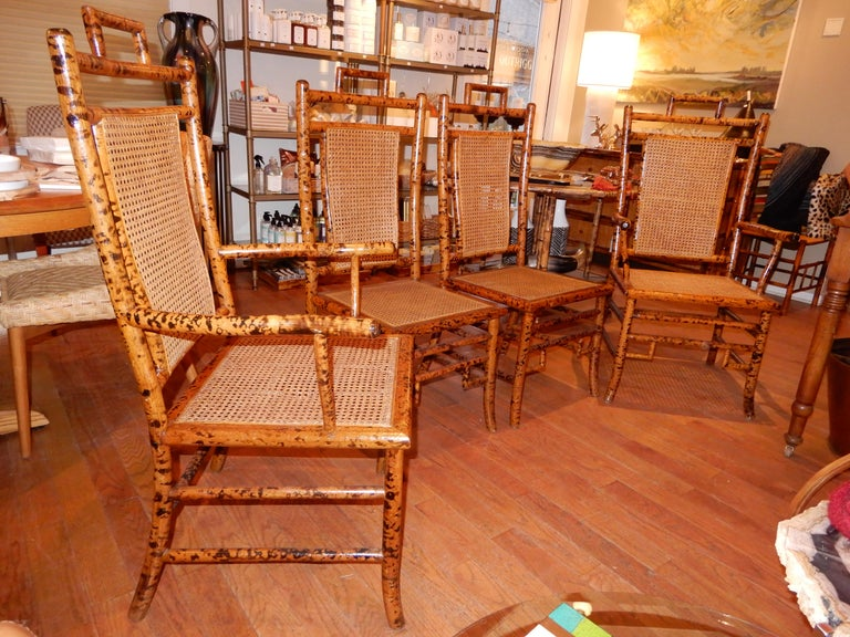 Four bamboo and cane hand crafted chairs, two with arm rests, two without. The bamboo frames have the classic torched flamed work throughout, original cane seats in immaculate condition, four beauties, click through to see the matching bamboo