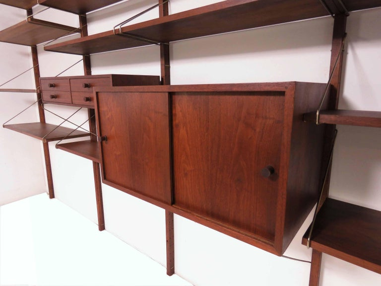 Midcentury wall-mounted shelving unit in walnut, circa 1960s. Four bay unit consists of a cabinet, drawer space and shelving. 