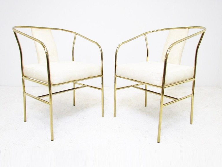 Set of four classic Hollywood Regency style armchairs by Milo Baughman for Thayer Coggin. The chairs have brass tube frames. Seats and backs upholstered in white. These can be used as lounge chairs as well as dining chairs.