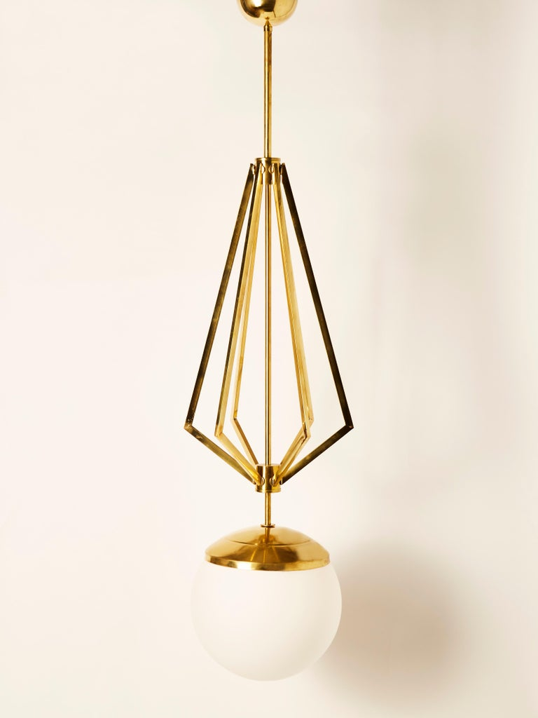 Four suspensions made of a central brass stem, decorative symmetrical rods and a large white glass globe housing a single light source.