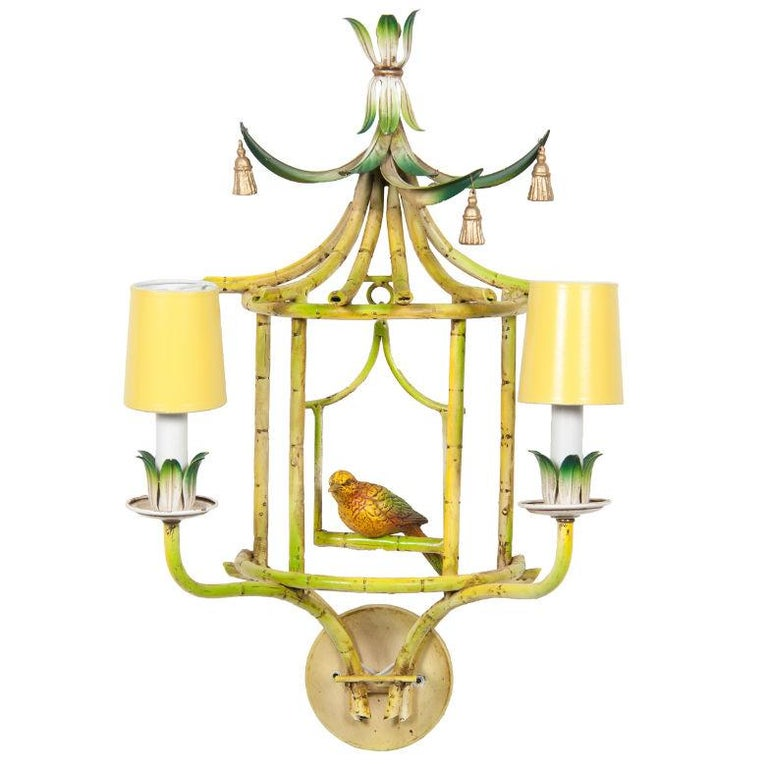 Very unusual chinoiserie wall sconces with hanging birds date from the mid-20th century, each having top with stylized leaves and frame painted to look like bamboo, including a hanging perch with bird in center, and two lights on front. Electrified.