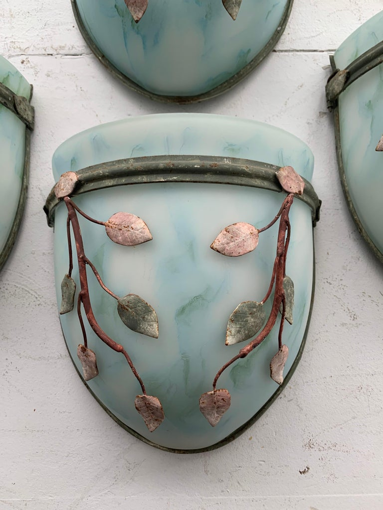 In the Tony Duquette style - these are four glass sconces with leaf-form metal decoration in light tones of blues and greens. Metal shows oxidization and age. Two blubs to interior and original wiring for use.