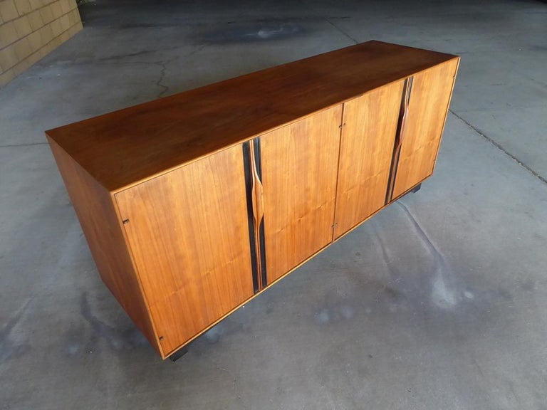 A four-door credenza/cabinet designed by John Kapel for Glenn of California in the 1960s. The cabinet is make of solid walnut, walnut vaneers and black laminate. Each door has a sculpted, integrated door pull and the base is ebonized.