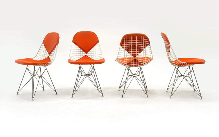 Set of four original white wire Charles and Ray Eames for Herman Miller white wire DKR dining chairs with original orange bikini covers. Zinc Eiffel Tower bases. All feet intact and original. Very good condition, ready to use.