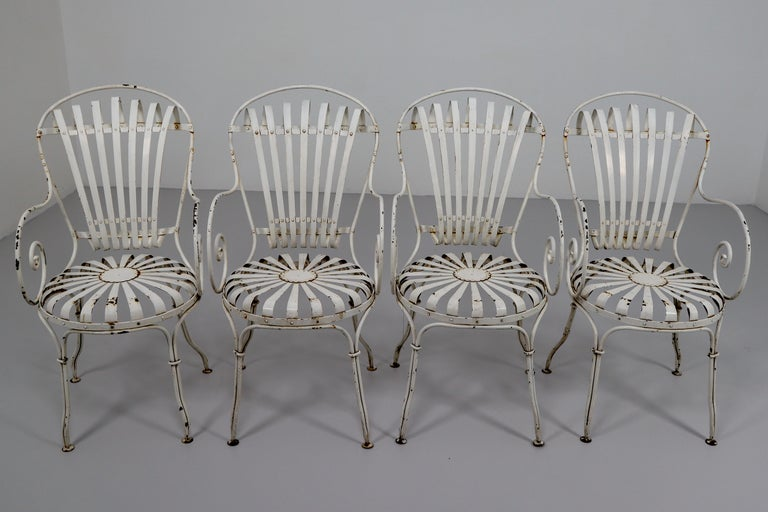 Pair of Four Francois Carre garden chairs manufactured, circa 1930 in France. Metal legs and structure, metal seat and backrest. In good vintage condition with minor wear consistent with a age and use, preserving a beautiful patina. This model of