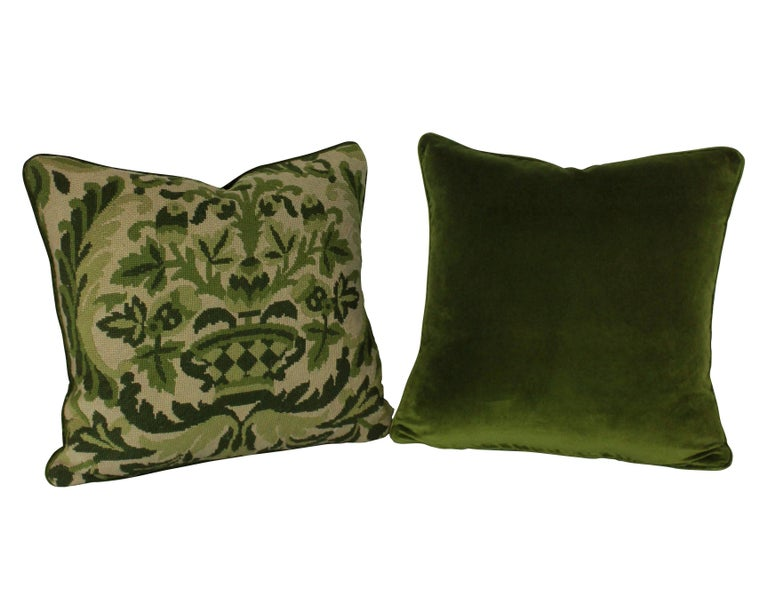 A set of four French 19th century needle point cushions of florid design in greens, with velvet backs and feather pads.