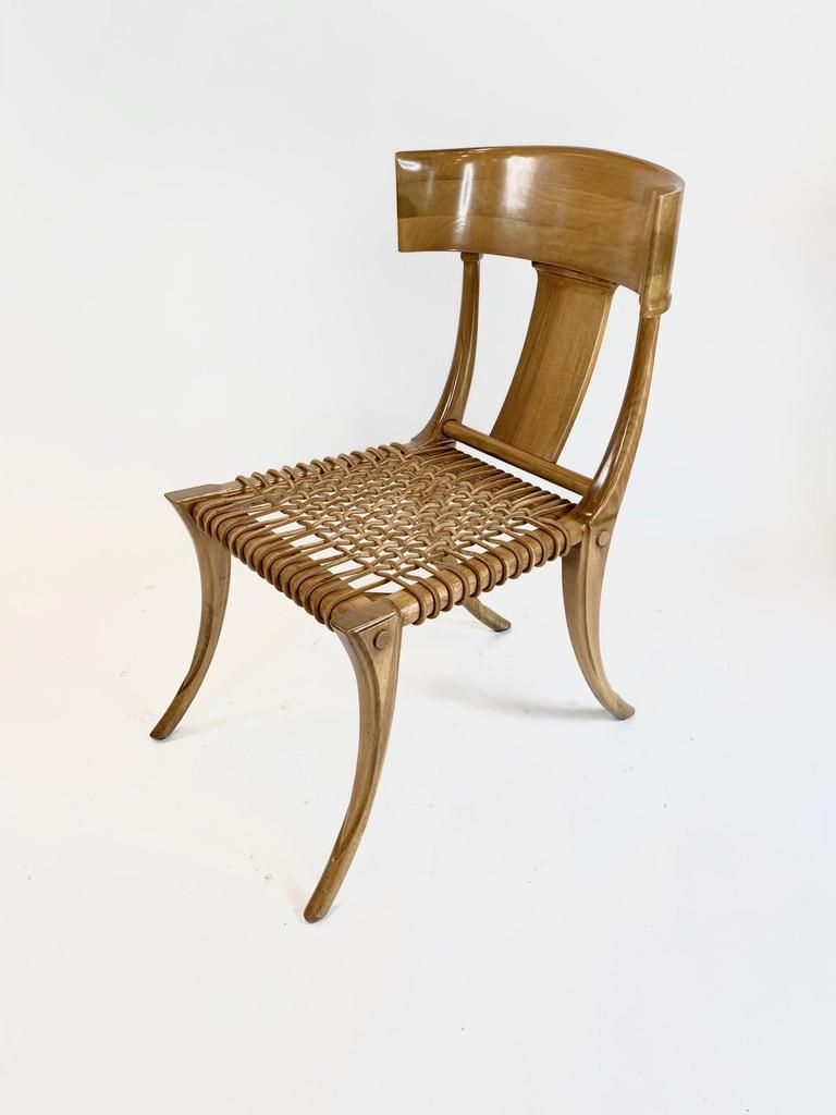 Set of four Kreiss Klismos Chairs in the style of TH Robsjohn Gibbings. Iconic splayed legs rise to support woven leather seat with arched back stretchers and curved solid wood back.