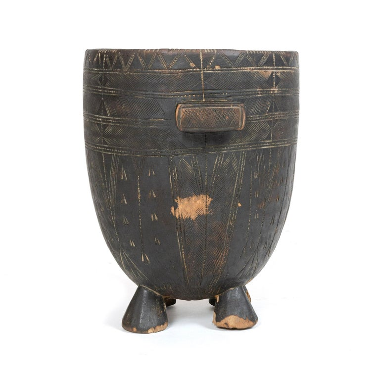 A robust vessel with a single handle on four legs, carved from one continuous piece of wood.