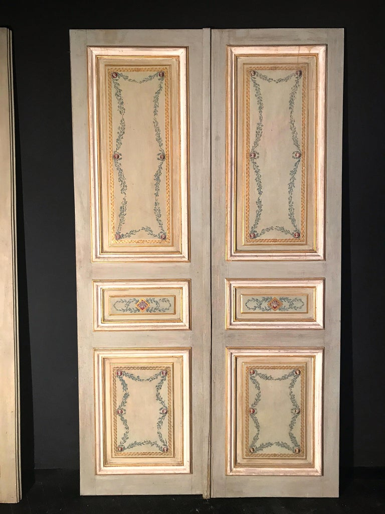Elegant Italian finely paneled wooden doors, decoratively painted, from the mid-19th century. The doors feature a single front recessed panel painted with foliage and geometric designs in various shades of gray, light blue and ivory color centered