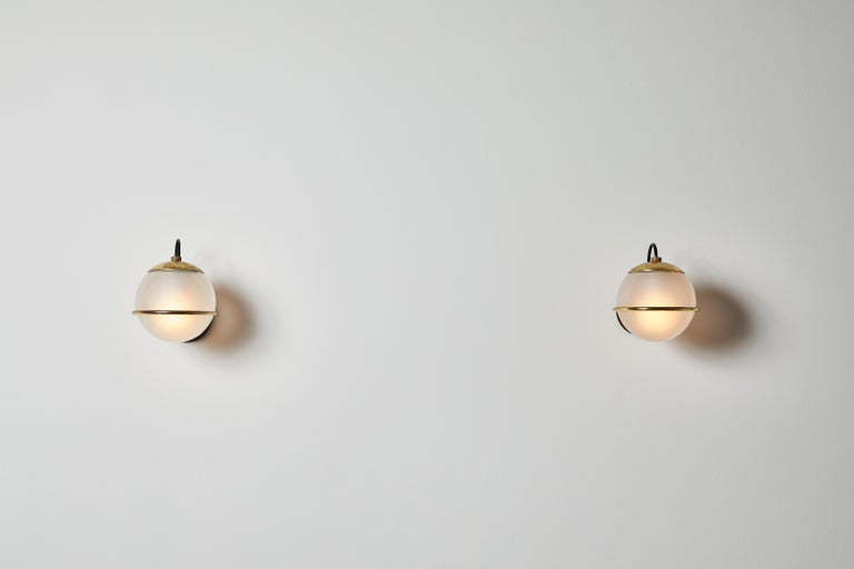Four pairs of Model 237/1 sconces by Gino Sarfatti for Arteluce. Designed and manufactured in Italy, 1959. Brass armature, opaline glass diffuser. Rewired for U.S. junction boxes. Each light takes one 60w European candelabra bulb. Bulbs provided as