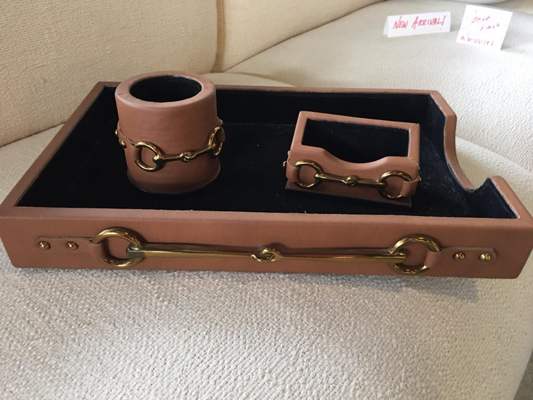 A gorgeous four piece desk set in leather and brass detail by Maitland Smith hand made in the Philippines. Very much in the style of Gucci with brass horse bits. Never used. From a chic Palm Springs Estate. Letter tray, covered box, pencil holder