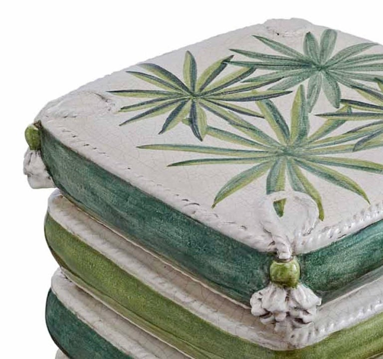 This refined object is handcrafted of ceramic and features four stacked pillows with a delicate palm leaf decoration in hues of light and dark greens set against a white background. The square shape of each pillow has a detailed trim along the