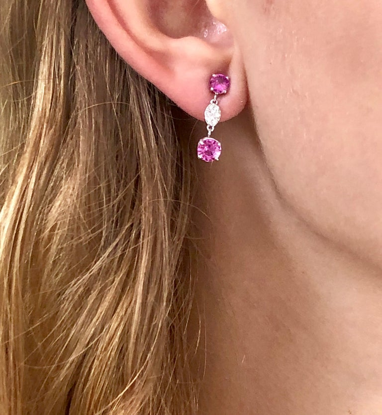Fourteen karat white gold diamond and pink sapphire earrings one inch long Four pink Sapphire Weighing 2.10 carats  Four  intense vivid pink matched sapphires Diamonds weighing 0.22 carat New Earrings Gold earrings are hanging off a post and with