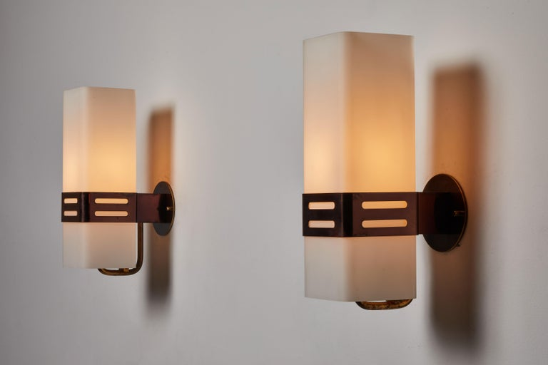 Pair of sconces by Stilnovo. Designed and manufactured in Italy, circa 1960s. Brass with brushed satin glass diffusers. Rewired for US junction boxes. Each light takes one E27 75w maximum bulb. Retains original manufacturers label. QTY: 2 sconces