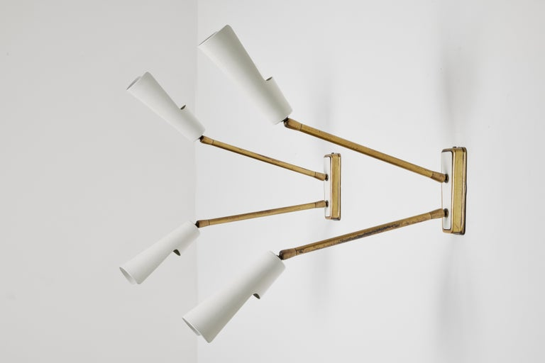 Four sconces by Stilnovo. Manufactured in Italy, circa 1950's. Enameled metal, brass. Original backplates. Wired for U.S. standards. Arms and shades pivot to various positions. We recommend one E14 European candelabra 60w maximum bulb per fixture.