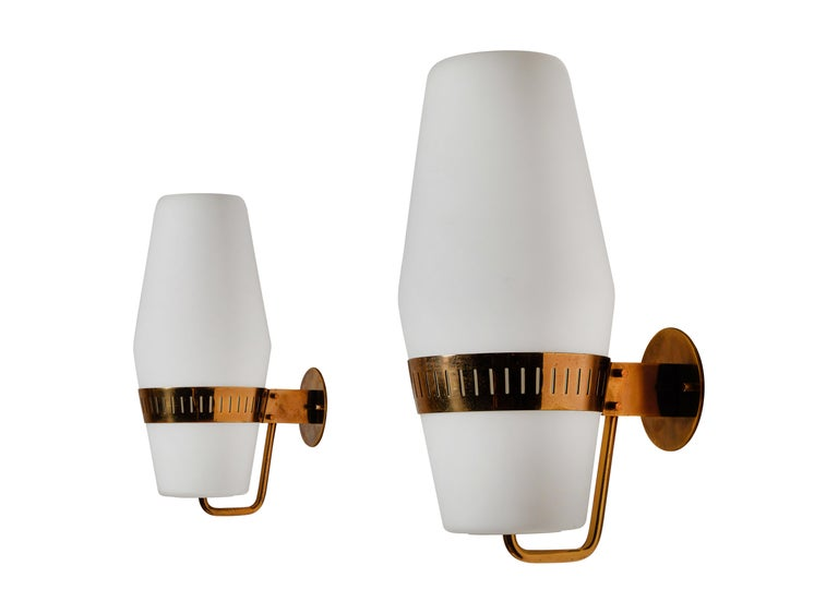 Four sconces by Stilnovo. Manufactured in Italy, circa 1950s. Brass with brushed satin glass diffusers. Rewired for US junction boxes. Each light takes one E27 100w maximum bulb. Retains original manufacturer's label. Priced and sold individually.