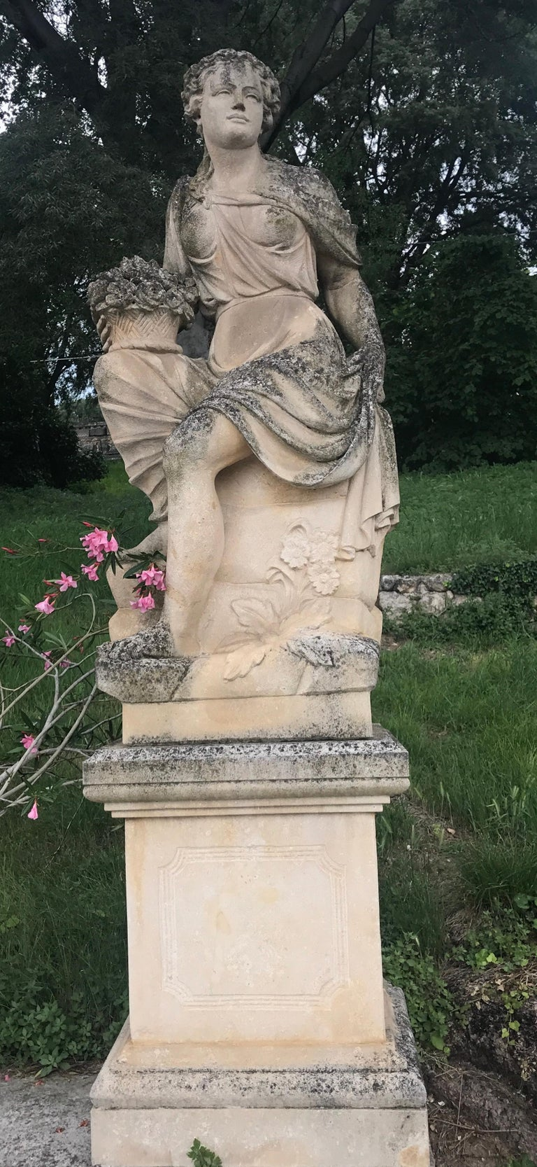 Set of outstanding italian stone statues representing the four seasons,  with seating classically draped female figures and their distinguishing symbols.  Autumn, winter, spring and summer.   Measures: Height cm 170 with square form bases cm H