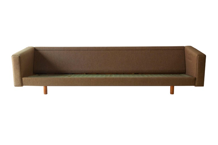 An extra large version of the Wegner sofa for GETAMA. The four-seat sofa is preserved with original striped wool upholstery and oak hardwood legs.   Frame is in good sturdy condition while cushions have some small holes at corners. Not very