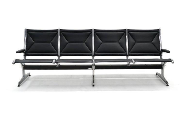 Tandem sofa seating for four designed by Charles and Ray Eames for Herman Miller. This piece only has arms on each end so is much more inviting for residential or office use. Very good condition. Black leather and cast aluminum. Ready to use.